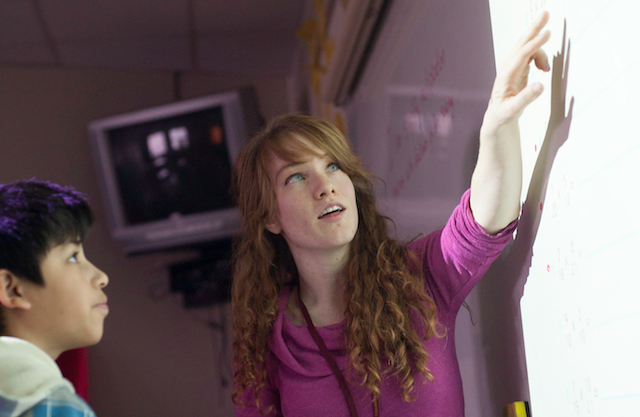 Teacher pointing to overhead projector screen.