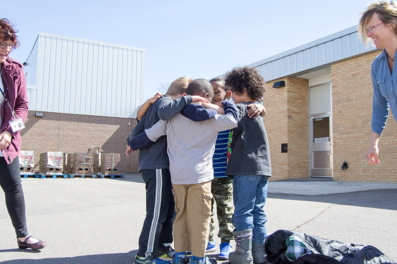 kids huddling outside New Hope Learning Center