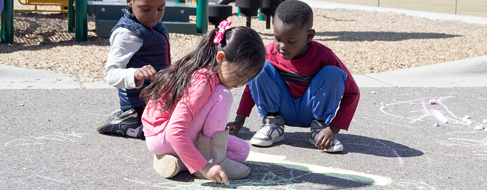 preschoolers play with chalk on playground